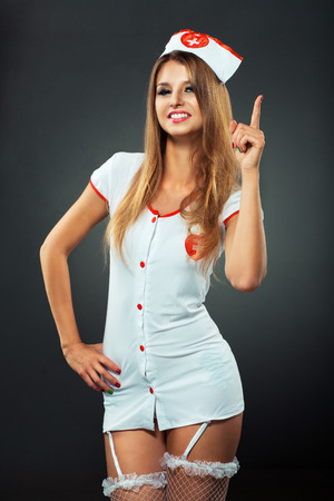 Young and beautiful dancer in nurse costume posing on studio background