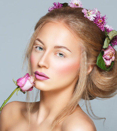 Lovely model with shiny volume curly hair with flowers, winter white eyelashes make-up, vivid lips and pink cheeks. Christmas look photo