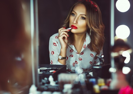 applying: Young beautiful girl doing makeup with red lipstick Stock Photo
