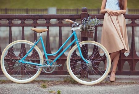 自転車を持つ若い美しい、エレガントな服装の女性。美容・ ファッション ・ ライフ スタイル
