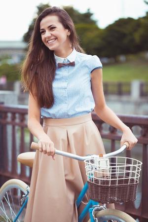 donna farfalla: Giovane bella, donna elegantemente vestita con la bicicletta.