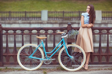 elegantly: Young beautiful, elegantly dressed woman with bicycle.