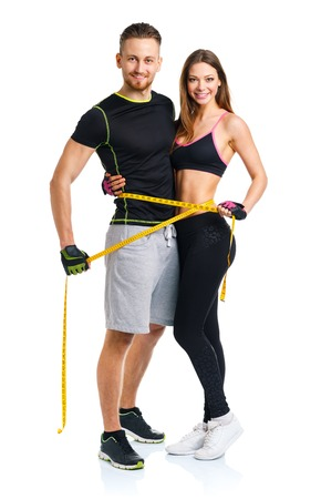 hand weight: Happy athletic couple - man and woman with measuring tape on the white background Stock Photo