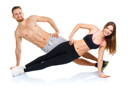 Athletic attractive couple - man and woman doing fitness exercises on the white background photo