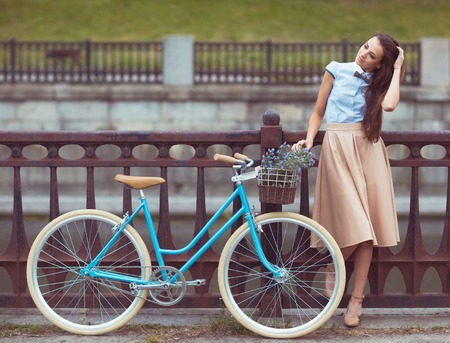 the skirt: Young beautiful, elegantly dressed woman with bicycle. Beauty, fashion and lifestyle