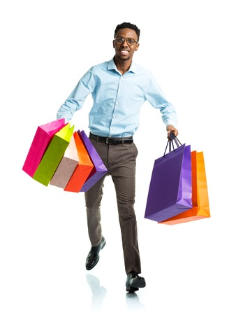 Happy african american man holding shopping bags on white background. Holidays concept photo