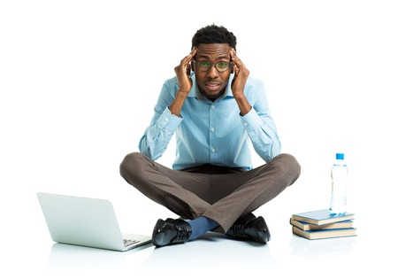Happy african american college student with laptop, books and bottle of water in stress sitting on white background photo