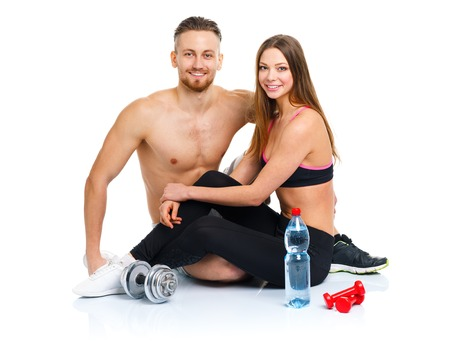 Athletic couple - man and woman after fitness exercise with dumbbells and bottle of water sitting on the white background photo