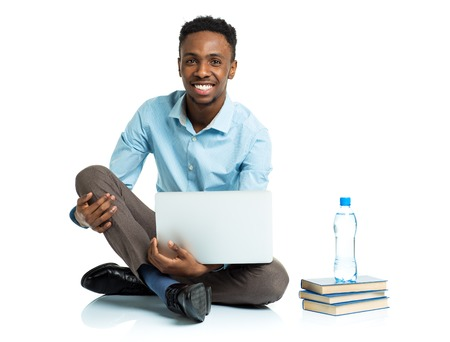 handsome student: Happy african american college student with laptop, books and bottle of water sitting on white background