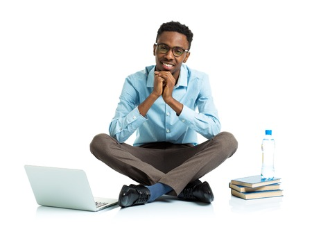 Happy african american college student with laptop, books and bottle of water sitting on white background photo