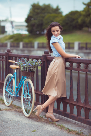 elegantly: Young beautiful, elegantly dressed woman with bicycle outdoor. Beauty, fashion and lifestyle Stock Photo