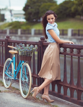 elegantly: Young beautiful, elegantly dressed woman with bicycle. Beauty, fashion and lifestyle