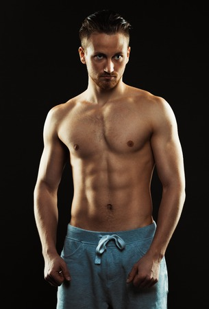 bare chested: Portrait of a shirtless confident young athletic man standing against black background Stock Photo