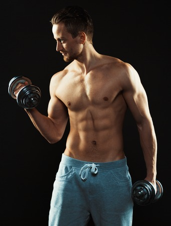 Athletic attractive man with dumbbells on the black background photo