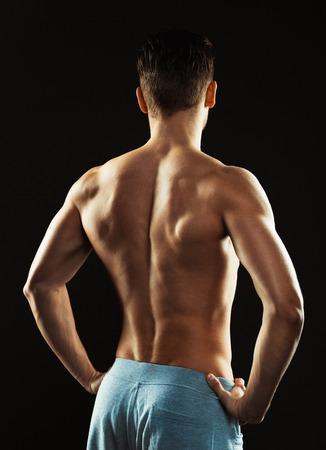 bare chested: Young athletic man showing his back on the black background Stock Photo