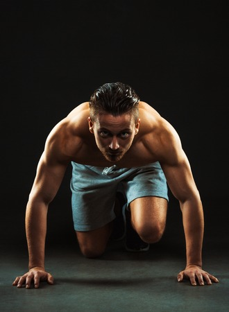 Sport attractive man doing fitness exercises on the black background
