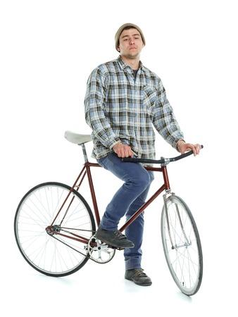 clavados: Hombre joven que hace trucos en bicicleta fija del engranaje sobre un fondo blanco