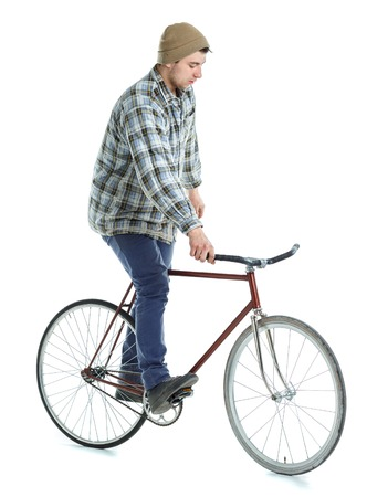 hand brake: Young man doing tricks on fixed gear bicycle on a white background