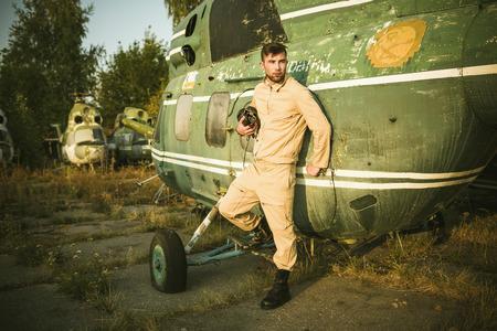 piloto: Piloto serio joven que presenta cerca del helicóptero
