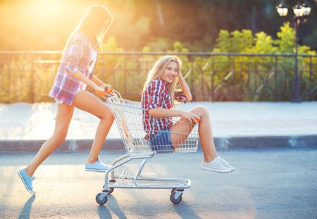 Twee gelukkige mooie tiener meisjes rijden winkelmandje buiten