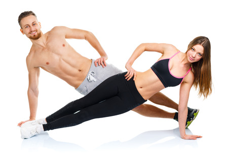 handsome young athletic: Attractive sport couple - man and woman doing fitness exercises on the white background Stock Photo