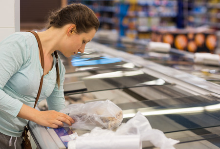produce departments: Beautiful young woman shopping in a grocery supermarket