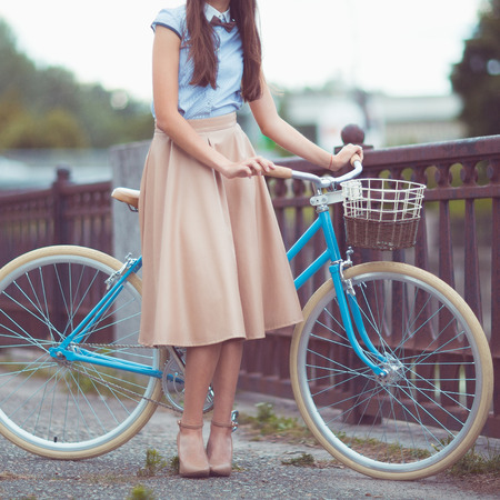 elegantly: Young beautiful, elegantly dressed woman with bicycle