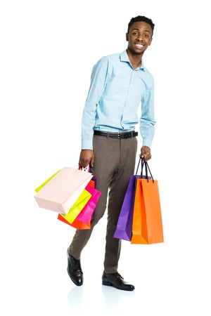Happy african american man holding shopping bags on white background. Shopping and holidays concept Stock Photo