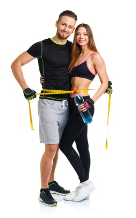 measure waist: Happy sport couple - man and woman with measuring tape on the white background Stock Photo