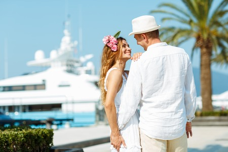 citytrip: Attractive young couple walking alongside the marina with moored boats on a luxury waterfront in summer sunshine