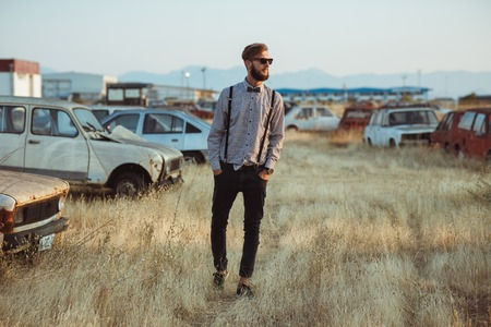 Portrait of a young handsome stylish man, wearing shirt and bow-tie on the field of old cars Stock Photo