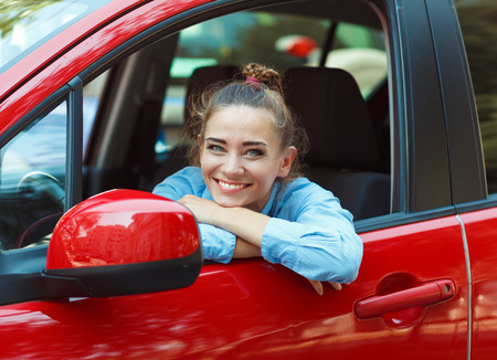 彼女の車を運転して若い笑顔の女性