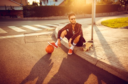 stylish man: Young stylish man in sunglasses with a basketball and skateboard sitting on a city street at sunset light Stock Photo