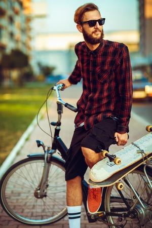 stylish man: Young stylish man in sunglasses riding a bike on city street
