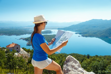 young people: Traveler girl searching right direction on map, traveling along Europe, freedom and active lifestyle concept