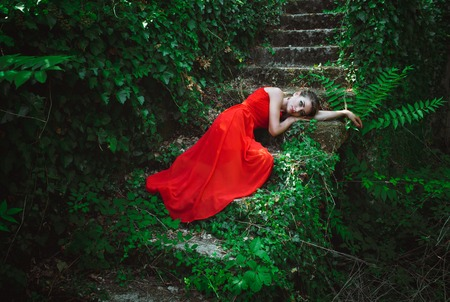 beautiful sad: Young beautiful woman in red dress lying on the steps of the old stairs in an abandoned yard Stock Photo