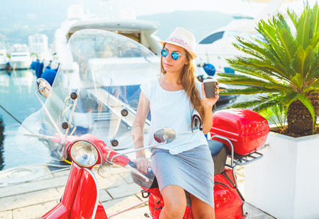 moped: Happy young trendy woman drinking takeaway coffee near her red moped on the waterfront in the morning Stock Photo