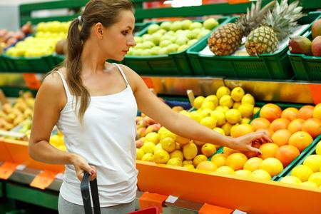 fruta: Joven y bella mujer de compras en un supermercado en el departamento de frutas y hortalizas