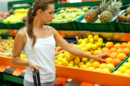 Young beautiful woman shopping in a supermarket in the department of fruit and vegetables Фото со стока