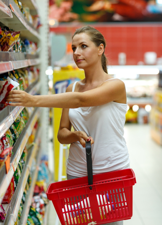 basket: Beautiful young woman shopping for cereal, bulk in a grocery supermarket