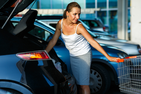 woman shopping cart: Young happy beautiful woman shifts the purchase from shopping cart in the trunk of a car on the parking Stock Photo