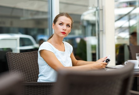 attractive  female: Attractive young woman with red lips reads a newspaper sitting in a cafe