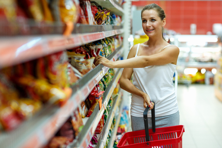 produce departments: Beautiful young woman shopping for cereal, bulk in a grocery supermarket
