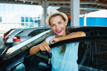 car dealer: Young happy woman standing near a car with keys in hand - concept of buying a used car Stock Photo