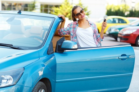 car rent: Young pretty woman in sunglasses standing near convertible with keys in hand - concept of buying a used car or a rental car