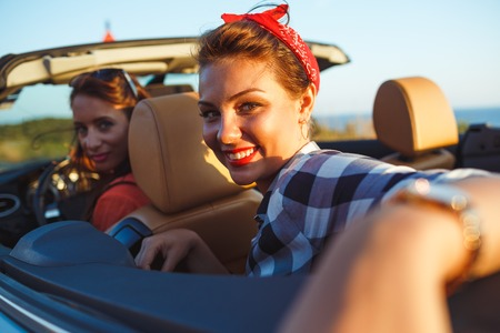 convertible: Two young happy girls driving a cabriolet Stock Photo