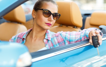 convertible car: Young pretty woman in sunglasses sitting in a convertible car with the keys in hand - concept of buying a used car or a rental car