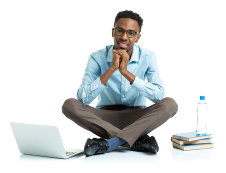 african student: Happy african american college student with laptop, books and bottle of water sitting on white background