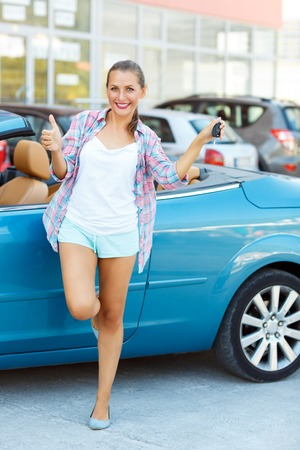 thumb keys: Young happy woman standing near a convertible with the keys in his hand and thumb up - concept of buying a used car or a rental car