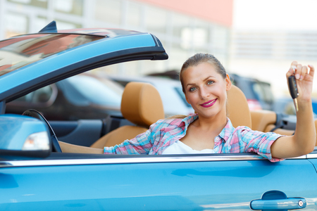 convertible car: Young pretty woman sitting in a convertible car with the keys in hand - concept of buying a used car or a rental car